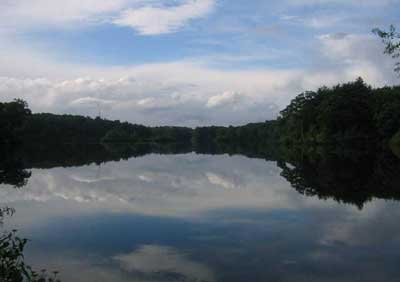 A picture of a mirror-like lake reflecting a blue sky, clouds and the distant shore